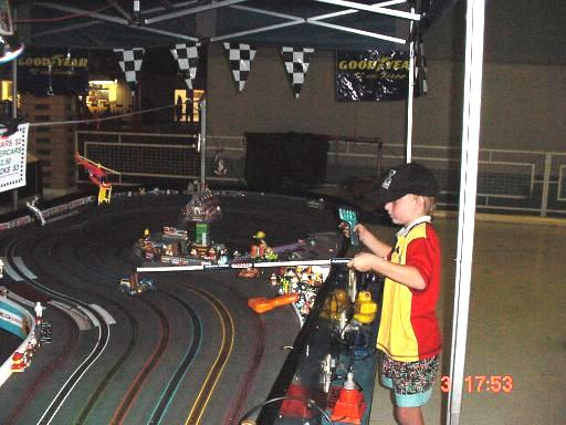 Leo playing on the slot car track, recovering his car after a crash